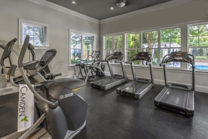 Fitness center with cardio equipment overlooking pool