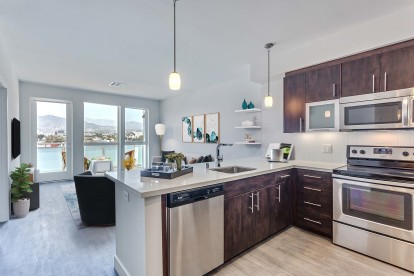 Kitchen with stainless steel appliances wood look flooring and patio views