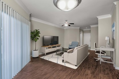 Living room with work from home space ceiling fan wood look flooring and sliding glass doors to patio