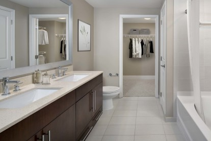 Warm modern style bathroom and large walk-in closet