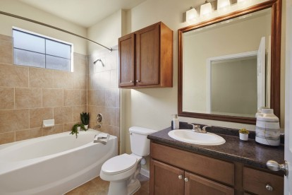 Bathroom with bathtub with tile surround and curved shower rod tile floors and framed mirror