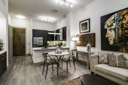 Open concept living and dining room with wood look flooring and track lighting