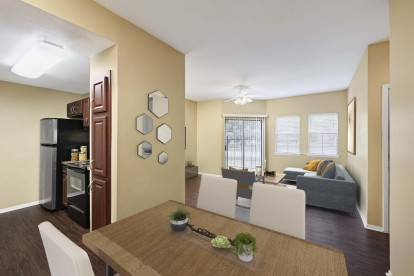 Dining and living room with wood look flooring ceiling fan and sliding glass doors to patio