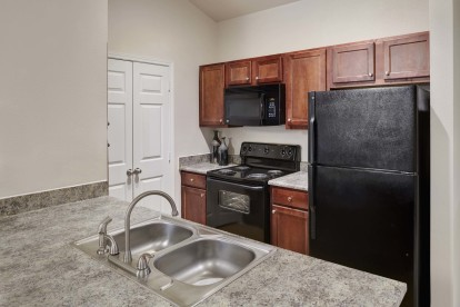 Kitchen with granite style countertops and black appliances alongside laundry area
