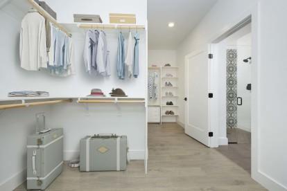 Spacious ensuite walk-in closet with wood shelves and light oak hardwood flooring