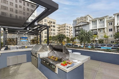 Barbecue grilling stations with bar stool seating near secondary pool and outdoor seating area