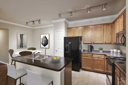 Kitchen with black appliances granite style countertops island and crown molding