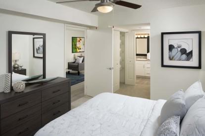 Bedroom with ensuite bathroom ceiling fan and carpet flooring