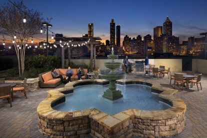Outdoor rooftop resident lounge with seating dining and barbeque areas