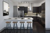 The terrace kitchen with glass cooktop, stainless steel appliances, bar seating, and mosaic tile backsplash