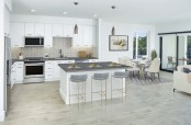 Open concept kitchen with stainless steel appliances, space for bar stool seating, dining area, and patio