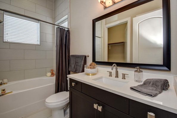 The townhomes bathroom with bathtub and shower combination, framed mirror, and under-mount quartz countertop sink