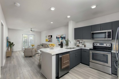 Open concept floor plan kitchen and living area with wood look floors french doors to private balcony and ceiling fan