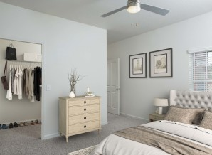 Bedroom with lighted ceiling fan and spacious walk in closet