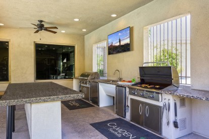 Two barbecue grilling stations with tv ceiling fans island seating and granite countertop