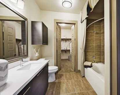 Bathroom with walk in closet bathtub with tile surround and curved shower rod and undermount sink