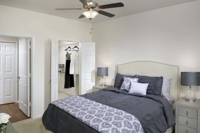 Spacious bedroom with ceiling fan and walk-in closet
