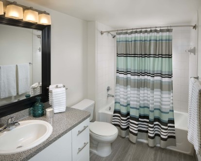 Bathroom with wood look flooring framed mirror and bathtub with tile surround and curved shower rod