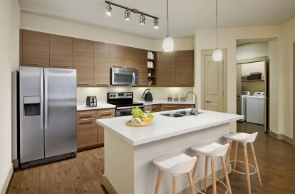 Kitchen and laundry with island white quartz countertops and stainless steel appliances