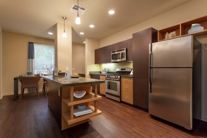Kitchen with wood style flooring and stainless steel appliances and dining area