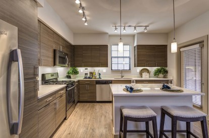 Open concept kitchen with stainless steel appliances white quartz countertops and barstool island seating