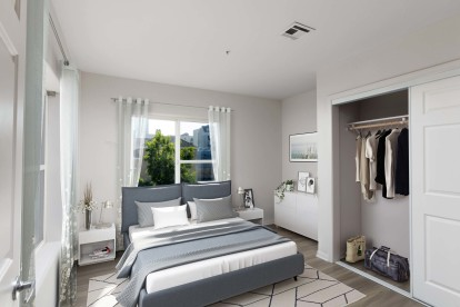 Bedroom with closet with sliding doors and wood look flooring