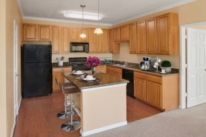 Kitchen with large island, granite countertops and black appliances