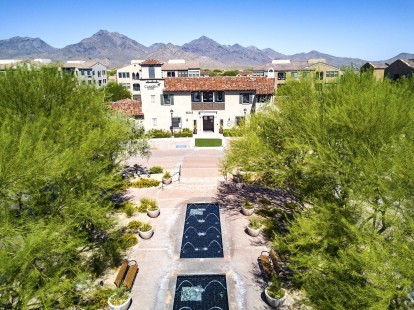 Aerial view of landscaped grounds with water fountains and camelback mountains in background