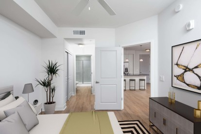 Bedroom with ensuite bath large closet ceiling fan and wood look flooring