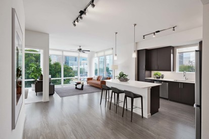 Open concept floor plan with floor to ceiling windows wood style flooring and ceiling fan