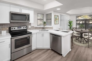 Open-concept windowed kitchen with stainless steel appliances and dining room