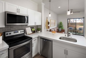 Open-concept kitchen with white quartz countertops, gray subway tile backsplash, and stainless steel appliances