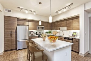 Kitchen with island barstool seating stainless steel appliances and white quartz countertops