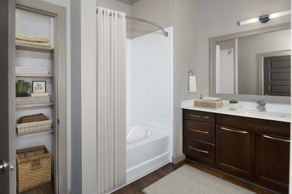 Terrace Bathroom with white quartz countertops, bathtub and shower combination, and linen closet with built-in shelving.