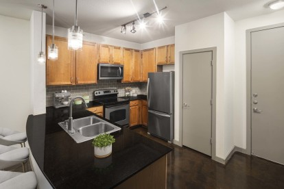 Kitchen with granite countertops stainless steel appliances and concrete flooring
