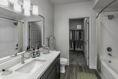 Bathroom including walk in closet and bathtub