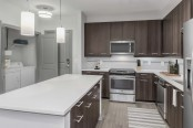 Ktichen with white quartz countertops, sleek gray cabinetry, and island