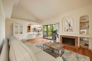 Open concept living room with fireplace wood look flooring and sliding doors to patio