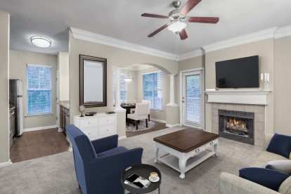 Living room with carpet flooring ceiling fan and crown molding open to kitchen and dining areas