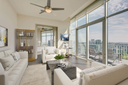 Camden Music Row Apartments Penthouse living room with floor-to-ceiling windows, large patio with downtown view, ceiling fans, and hardwood-style flooring