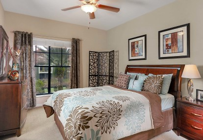 Bedroom with large windows natural light and ceiling fan