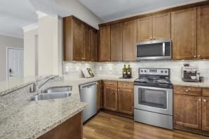 Spacious kitchen with granite countertops, subway tile backsplash, and hardwood-style flooring