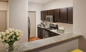 Kitchen with bar top seating and stainless steel appliances