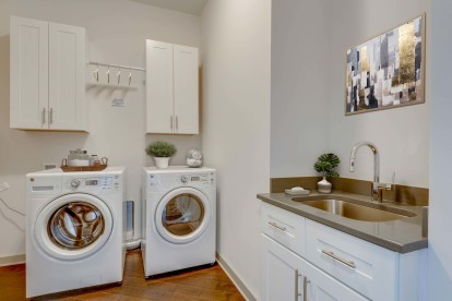 Camden Music Row Apartments Penthouse Utility Room with side-by-side front-loading washer and dryer, sink, cabinetry, and drying rack