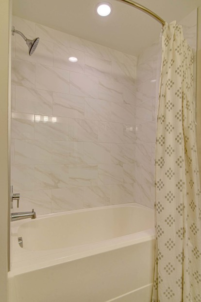soaking tub with marble-inspired tile surround