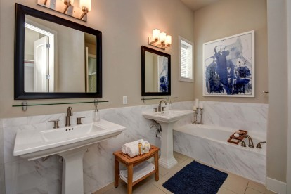 The townhomes bathroom with stand-alone vanities, tile flooring, and a bathtub