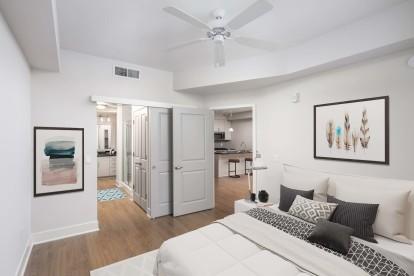 Bedroom with ceiling fan ensuite bathroom and wood look flooring