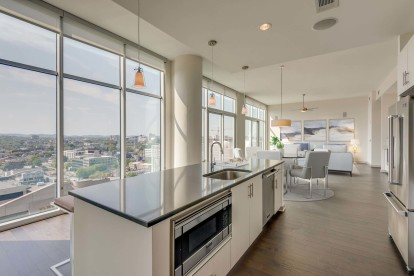 Camden Music Row Apartments Penthouse kitchen with island, floor to ceiling windows, room for dining, built-in appliances
