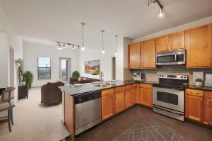 Kitchen with granite countertops wood look flooring and stainless steel appliances
