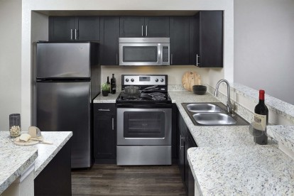 Expansive kitchen with stainless steel appliances including microwave